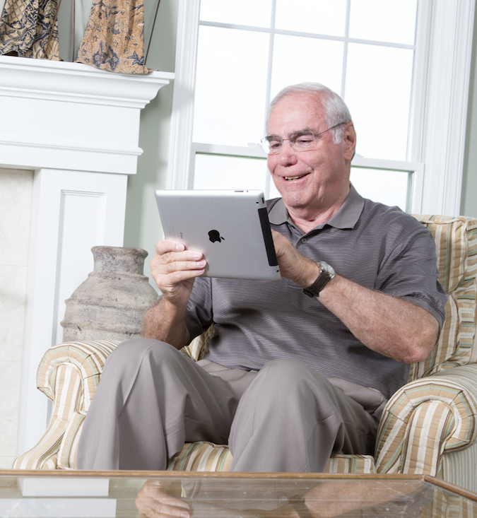 Senior playing on an iPad sitting in a chair smiling