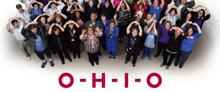 "Group of people spelling out ""O-H-I-O"" with their arms"