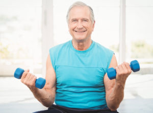 Older man lifts weights to improve emotional wellness