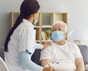 caregiver talks to senior man wearing mask