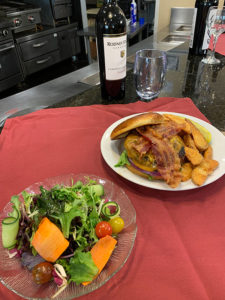salad and hamburger with home fries with wine