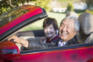 Smiling Asian senior couple in red convertible