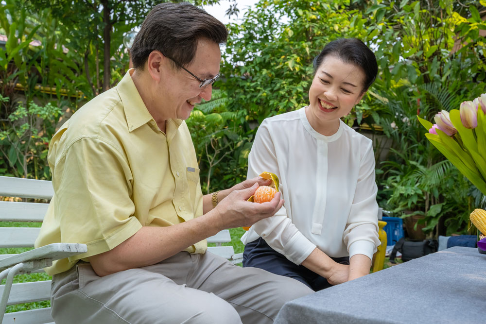 older asian couple eating oranges and talking about senior living