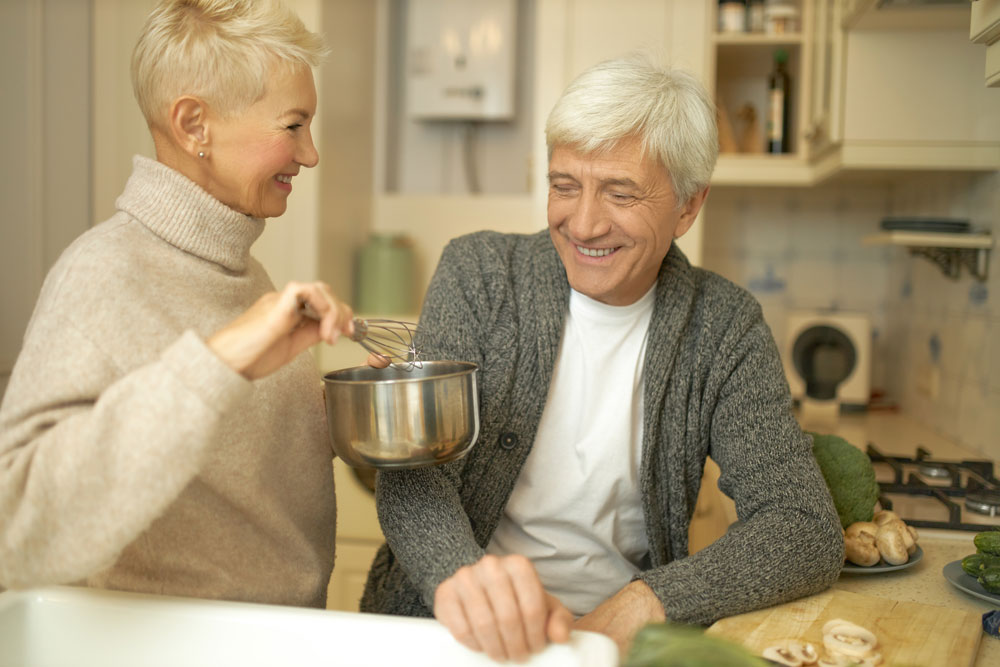 attractive older couple in kitchen talking about senior living options