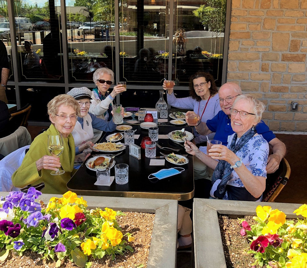 group of happy senior couples raising a toast during dinner