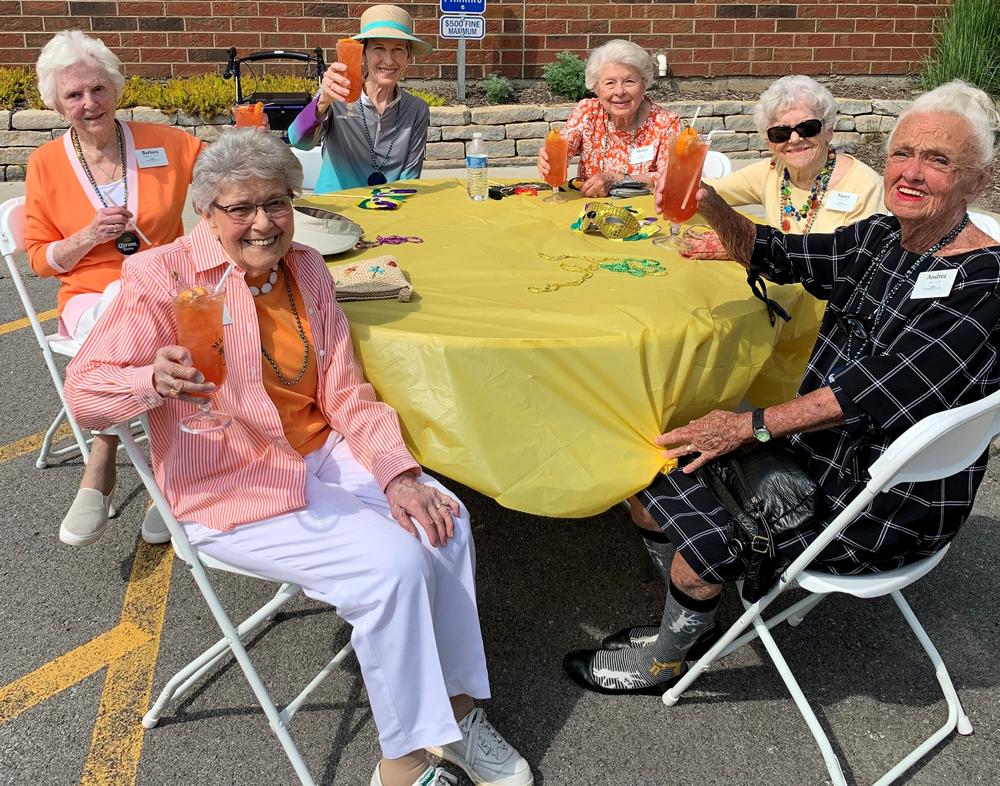 senior ladies raise their glasses while sitting at a round table